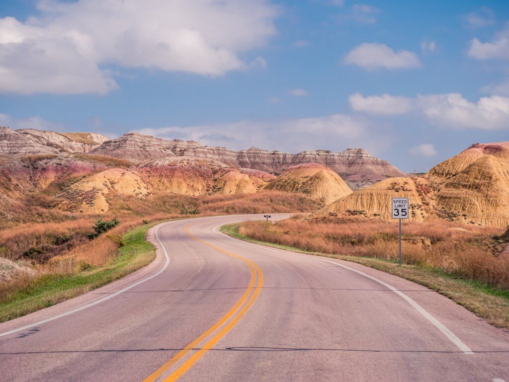 Winding road through colorful layered rock formations in Badlands National Park.