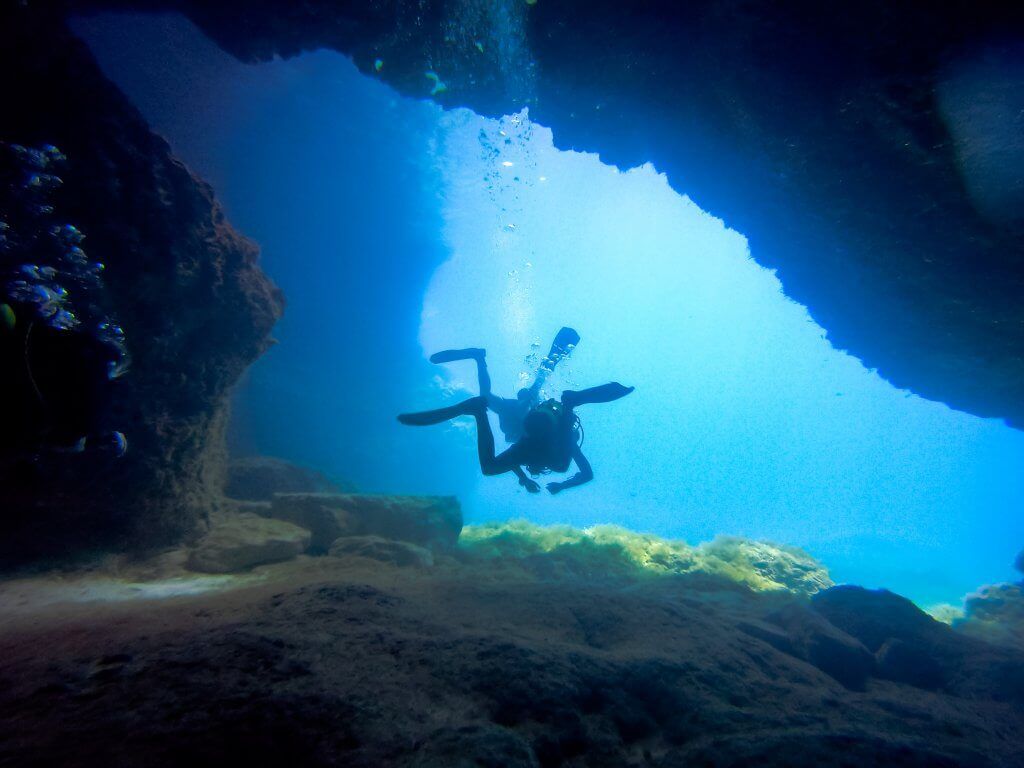 silhouette of two divers going through cave diving in malta