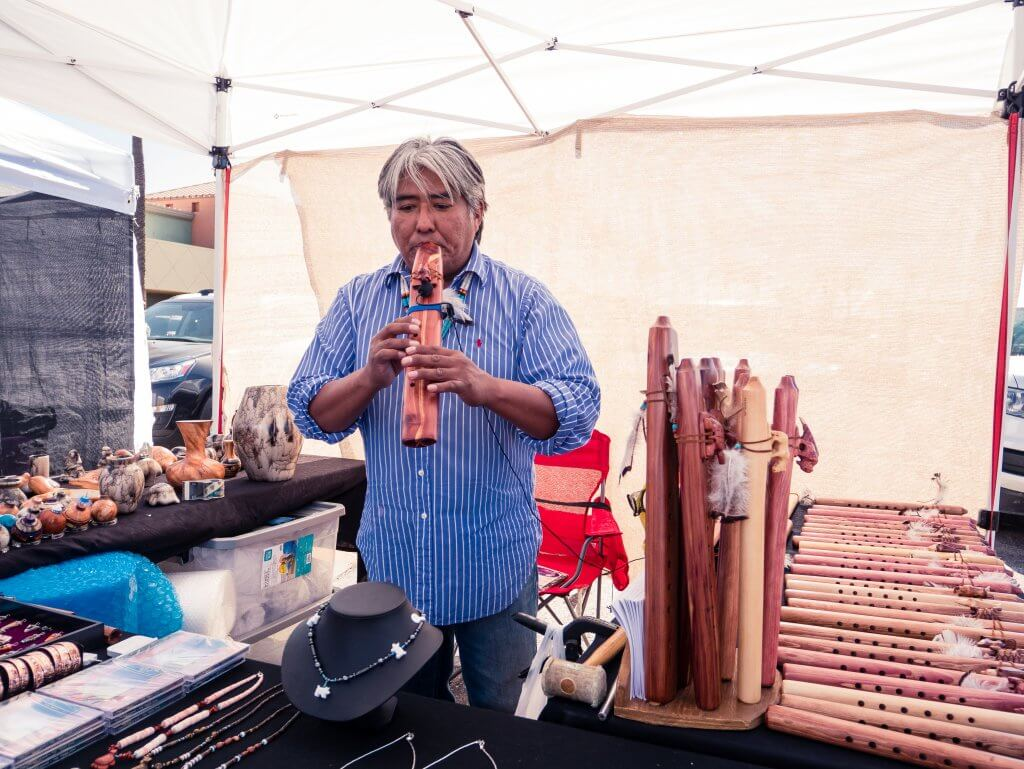 Navajo artist playing a wooden flute in art market stall