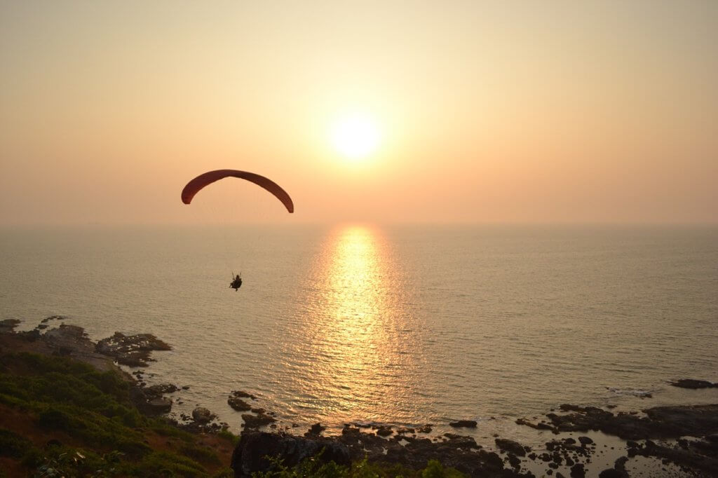 Orange sunset with silhouette of paraglider near Goa beach