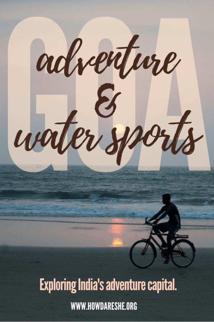 "Text ""adventure and water sports"" overlayed on the word ""Goa"" with an image of a cyclist's silhouette on the beach with the sunset and waves crashing in, additional text ""exploring India's adventure capital"""