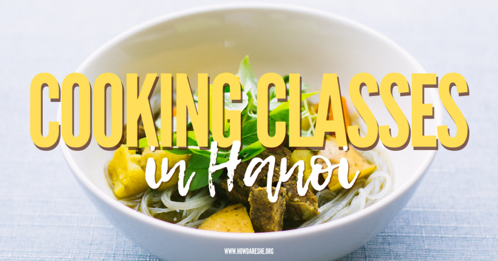 Text cooking classes in Hanoi over image of bowl with rice noodles, yelow and orange vegetables, meat and sprig of green herbs