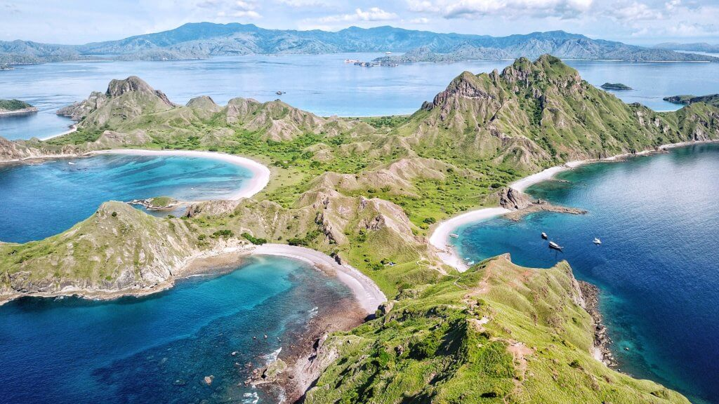 Aerial picture of Komodo National Park with sharp green mountains, sand and blue waters