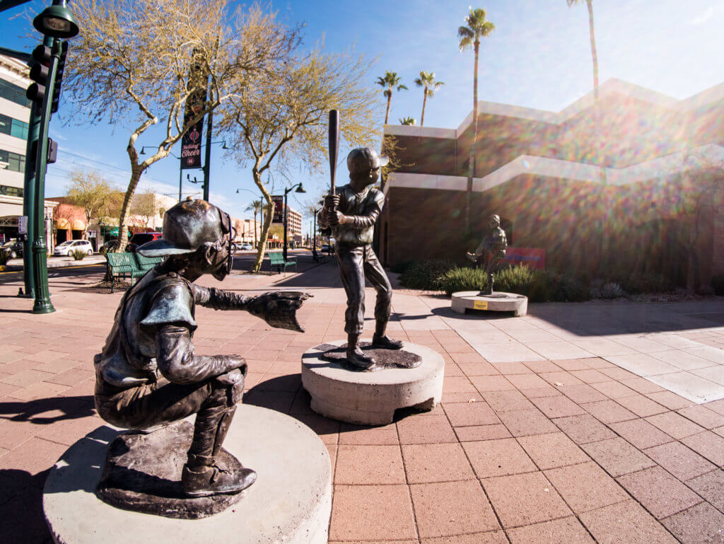 Two statues, metal in Mesa of young boys playing baseball, a batter and a pitcher