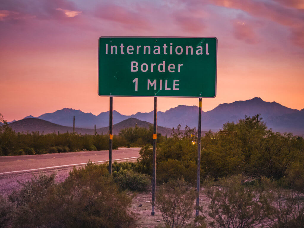"Pink, orange and purple sunset behind a road sign ""International Border 1 mile"""
