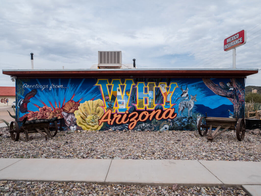 "Street art style mural of ""Why, Arizona"" with southwestern landscapes"