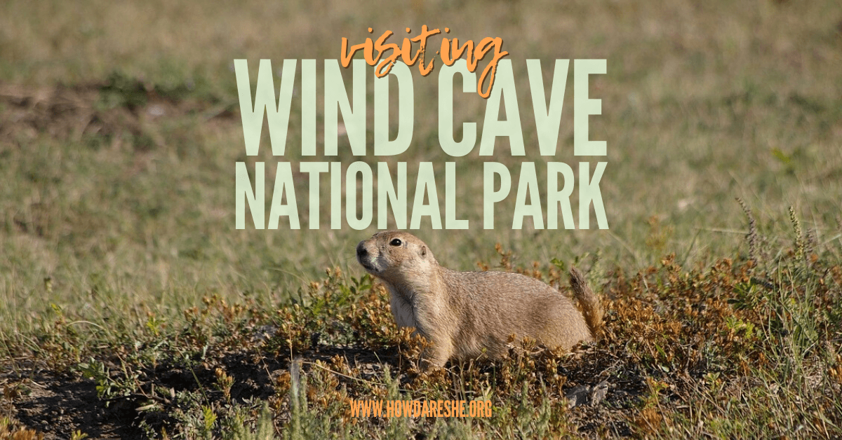 "Text, ""Visiting Wind Cave National Park"" overlay on iumage of small prairie dog in green and orange grass"