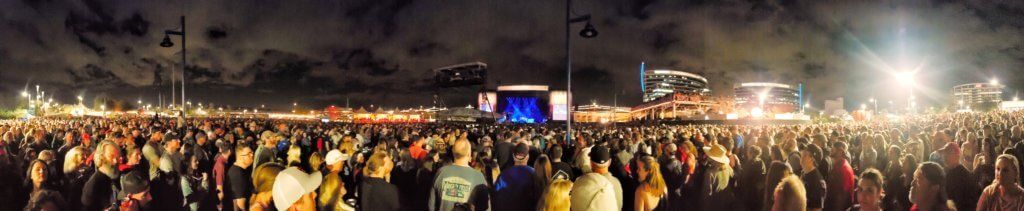 Panoramic of huge crowd at Dave Matthews Band set at Innngs Fest 2020 with the stage lit up blue in the center