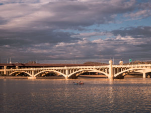 Golden hour light reflecting off the water of Tempe Town Lake with arched bridge in the background and two rowers in a kayak