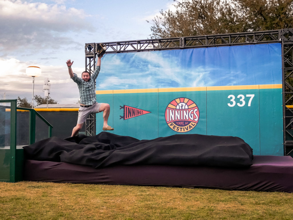 Man jumping on to padding for photo of a catch at Innings Fest 2020