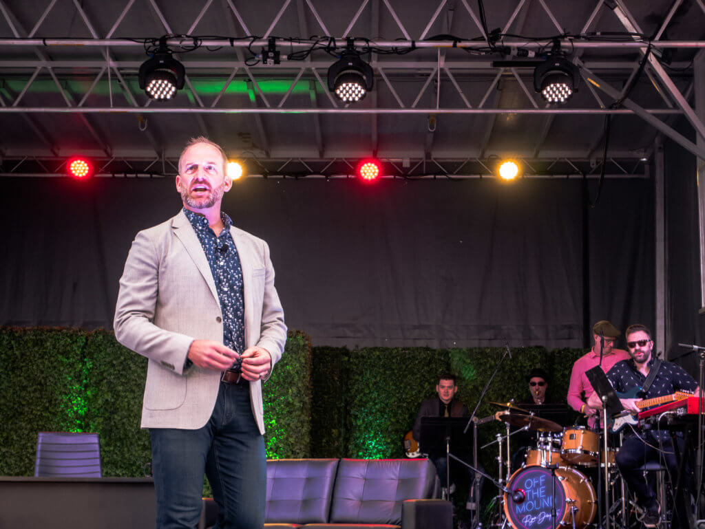 Ryan Dempster in a khaki blazer and jeans on stage with band in the background at Innings Fest 2020