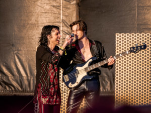 Lead singer of the Struts and guitarist sharing a microphone and laughing with golden hour sun at Innings Fest 2020