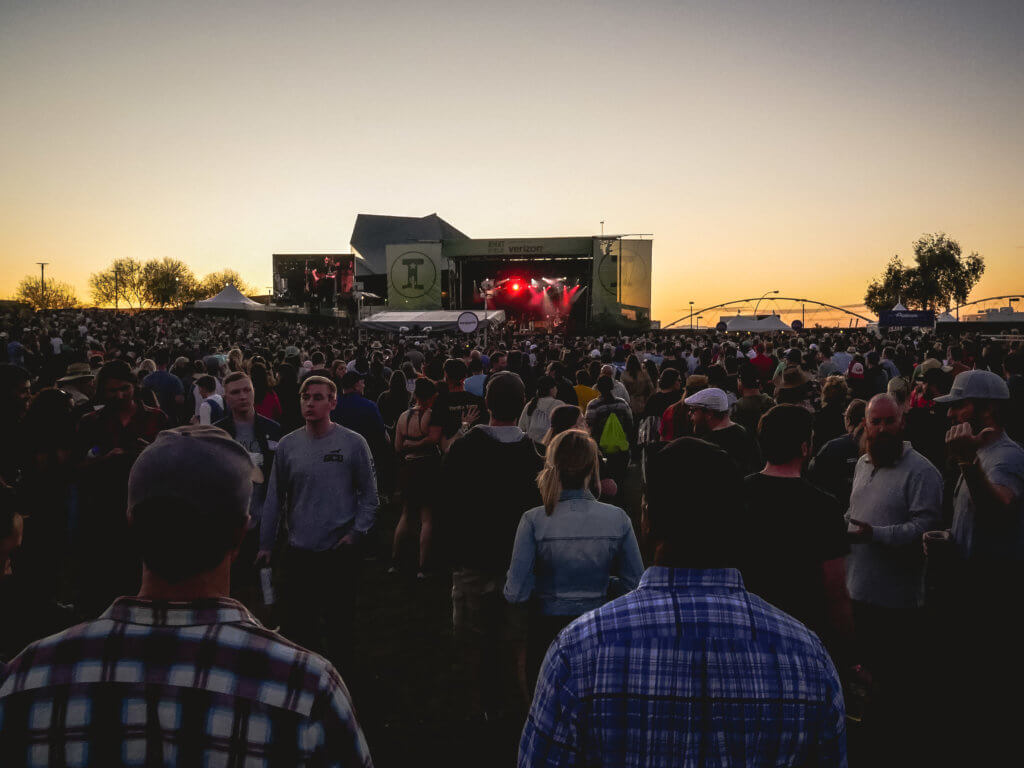 Sun setting behind Right Field stage at Innings Fest 2020, crowd going back for a long way