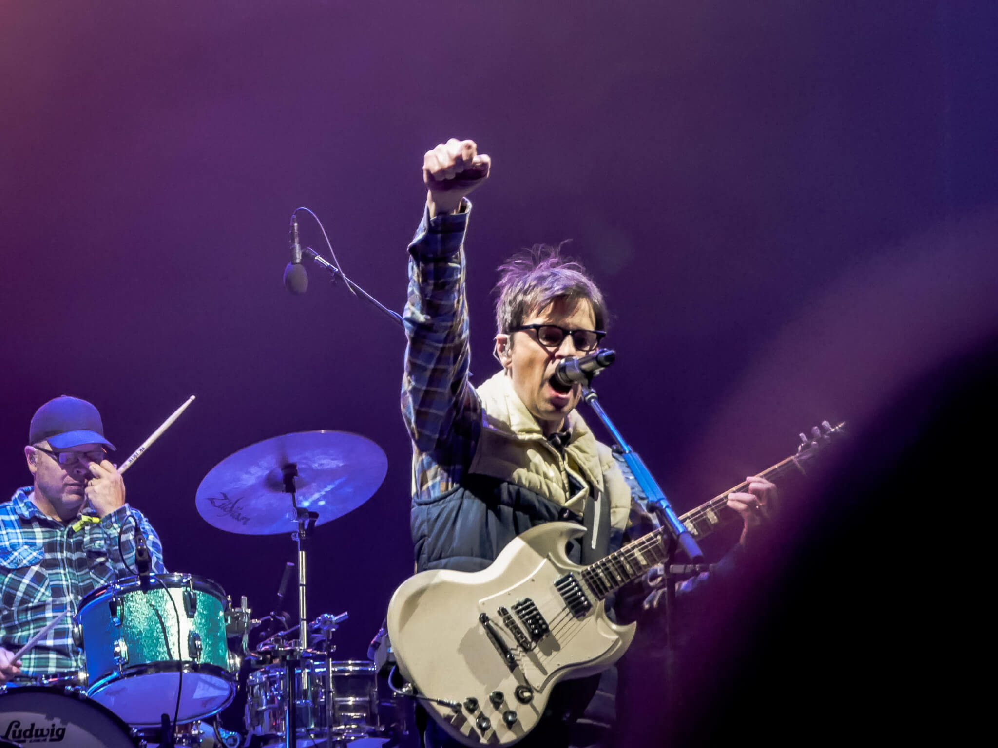 Weezer closing the night at Innings Festival; purple lights on the stage with drums and guitar.