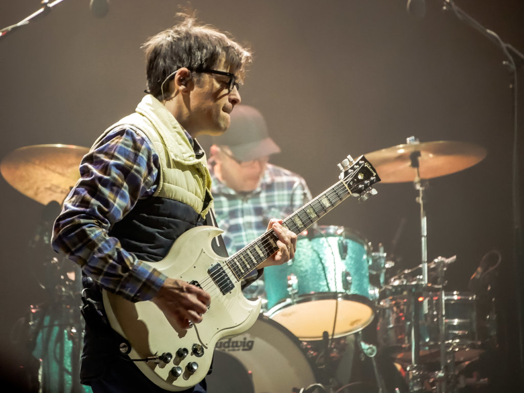 Rivers Cuomo playing guitar with drummer in the background as Weezer closed Innings Fest 2020