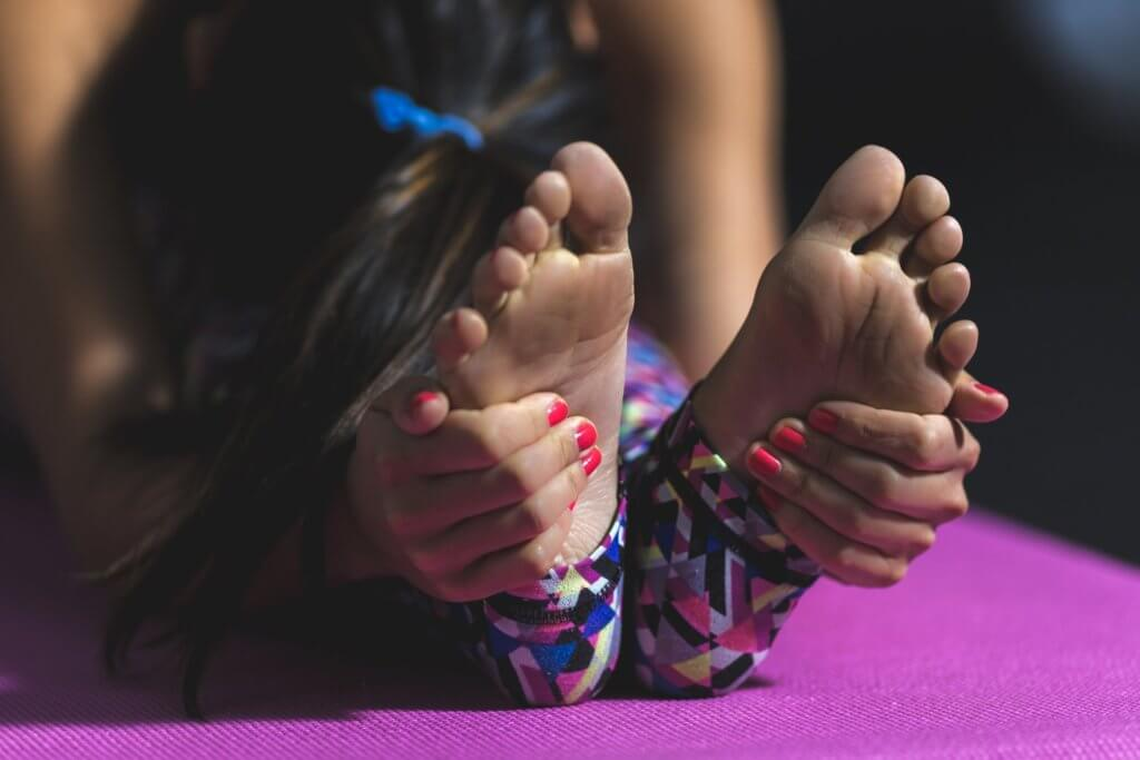 Woman stretching on purple yoga mat, folded with hands around feet